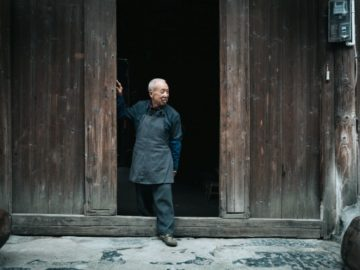 China Farmer in front of warehouse